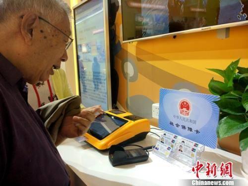 正在参观社保内容的退休老人。中新网记者 李金磊 摄